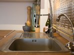 Sink with spring tap for ease in washing. Dishwasher available too.