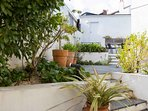 Our private terraced garden has BBQ & places to sit & enjoy the sunshine. Above is our garage.