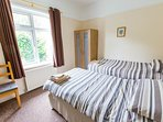Twin bedroom with two full size single beds, overlooks the side garden.