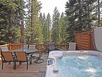 Large back deck, with a hot tub, furniture, and a grill