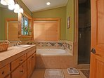 En suite bathroom with shower and jetted tub