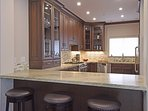 Modern kitchen, outfitted with a bar counter for casual meals