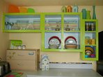 Kitchen w/display dishes on top shelf. User friendly dishes glasses and cups on bottom/side shelves