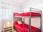 Dormitorio con litera de tres camas y TV