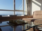 Relax to watch TV on our comfortable couches with large windows onto the sea