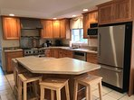 Large kitchen with stainless steel appliances and island.