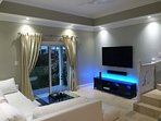 Modern living room featuring a brand new, state of the art 65' OLED TV by LG