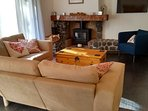 Living area with spacious corner sofa, tub chair, log burner and TV