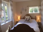 Cosy master bedroom overlooking the thatched listed cottages and farmland with ensuite shower room