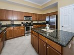 Spacious kitchen with plenty of countertop and cabinet space, utensils, cookware, etc.