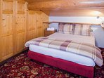 Camera da letto, stile alpine, letto matrimoniale con cuscini in piuma e piumone soffice e caldo