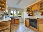 Well equipped kitchen with doorway to rear patio and rural views