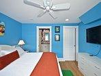 Master bedroom includes king sized bed, huge flat screen TV, closet, dresser, and en suite bathroom