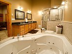 Luxurious master bathroom with dual sinks, huge walk-in shower, and jetted tub.