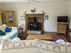 Front Room - Tastefully decorated with oak furniture, woodburner, TV, games cupboard and also a fan.