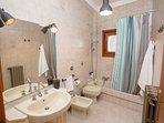 Bagno con lavabo e mobiletto, bidet, wc, vasca-doccia con tenda.