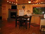 full kitchen with high dining table, all the windows face the river. rocked in propane fireplace, tv