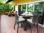Outdoor patio with sun chairs and dining