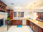 The kitchen has modern appliances with a breakfast bar with added space