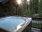 Private outdoor hot tub with forest views