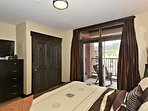 Master bedroom with balcony and flat screen TV