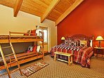 Main level master bedroom with a King bed, twin bunks, flatscreen TV and attached bathroom.