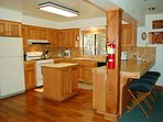 Kitchen, gas range, dishwasher all tiled counter top. Additional seating for four at counter