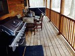 Large back deck with outside dining, hot tub and large gas grill