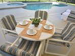 Outdoors eating area with pool view