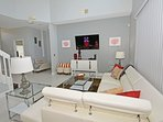 Family seating area with wall mounted flatscreen TV and leather corner sectional sofa