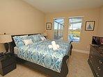 Master camera da letto 1 (piano inferiore) con vista piscina e TV a schermo piatto