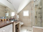 The bathroom with washing machine, shower cabin, large mirror, marble slab with designer glass wash.