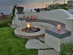Fire pit is adjacent to pool and outdoor grill center