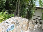 Native stone wall lines stairway entry from private parking area