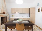 Cucina attrezzata con frigo-congelatore, forno, pentole, stoviglie, piatti, bicchieri
