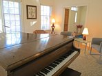 The baby grand piano is housed in the parlor off the front entryway