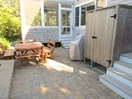 The stone patio just off the screened portch is a great place for outdoor meals.  Note the outdoor shower and gas...