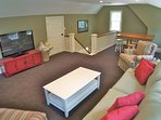 """The loft is located upstairs from the living area and has a 52"""" TV, a pullout couch, and a game table"""