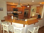 The well-equipped kitchen has newer appliances and a breakfast bar