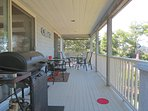 Covered deck with a gas grill and patio seating