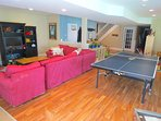 Spacious game room in the lower level with a wrap around couch, and flat screen TV. NOTE  The ping pong table is no...