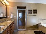 En suite master full bath with Jacuzzi tub, separate shower, and double sinks