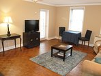 Flat screen TV,  desk and dining table with chairs