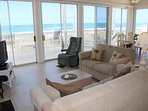 Oceanfront living room with floor to ceiling, wrap around windows.  Offering breathtaking views of the beach. The...