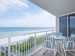 Private oceanfront balcony with table for 4 and lounge.