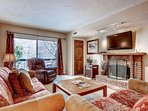 Spacious living room with comfortable seating for six (6), wood burning fireplace, private balcony and large HDTV.