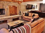 Living room with stone fireplace, lots of seating, and adjacent family room with 70' HD TV, Blue Ray DVD, and Wii U...
