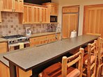 Kitchen with granite counters, Wolf gas stove, Sub Zero refrigerator, and 4-bar seats - Park City Tranquility - Park...