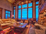 Living room with stone fireplace, cozy seating and amazing views of the ski slopes