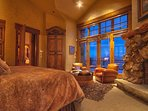 Typical master bedroom suite with king bed, stone fireplace, sitting area, and incredible bathroom